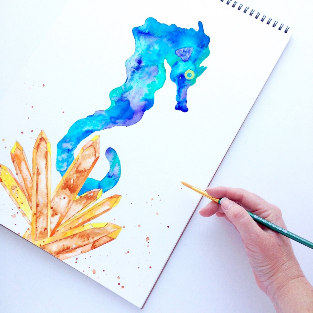 Watercolor painting by Mika Harmony of a Cerulean blue and teal green seahorse in a cluster of sunset crystals
